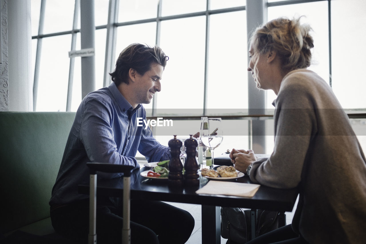 sitting, food and drink, table, indoors, food, adult, men, window, three quarter length, two people, meal, side view, eating, women, togetherness, communication, business, drink, real people, plate, couple - relationship