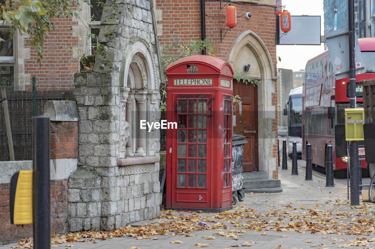 Red telephone booth against buildings in city during autumn