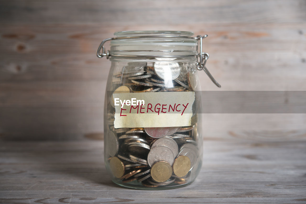 Close-Up Of Coins In Jar With Emergency Text On Table