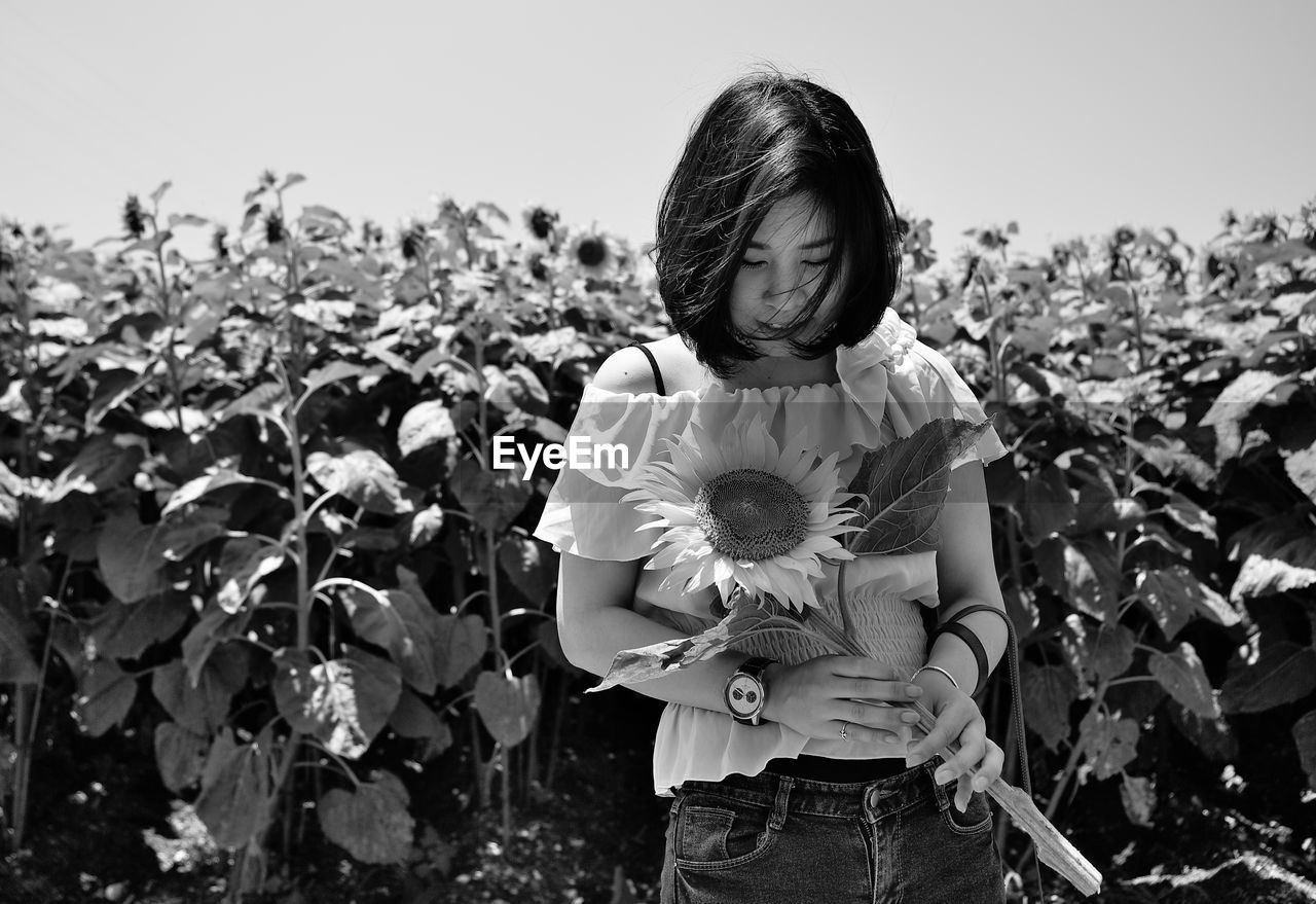 childhood, real people, girls, innocence, one person, field, growth, outdoors, front view, day, plant, rural scene, leisure activity, standing, nature, lifestyles, agriculture, child, flower, children only, clear sky, freshness, sky, people