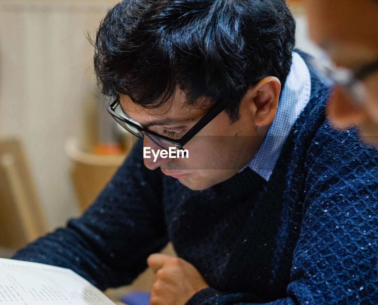 Eyeglasses  Real People Glasses One Person Focus On Foreground Sitting Indoors  Looking Down Men Looking Adult Lifestyles Concentration Casual Clothing Black Hair Close-up Young Adult Book Reading Menu Restaurant Thoughtful Choosing Decisions Head And Shoulders Asian Ethnicity Reading Glasses