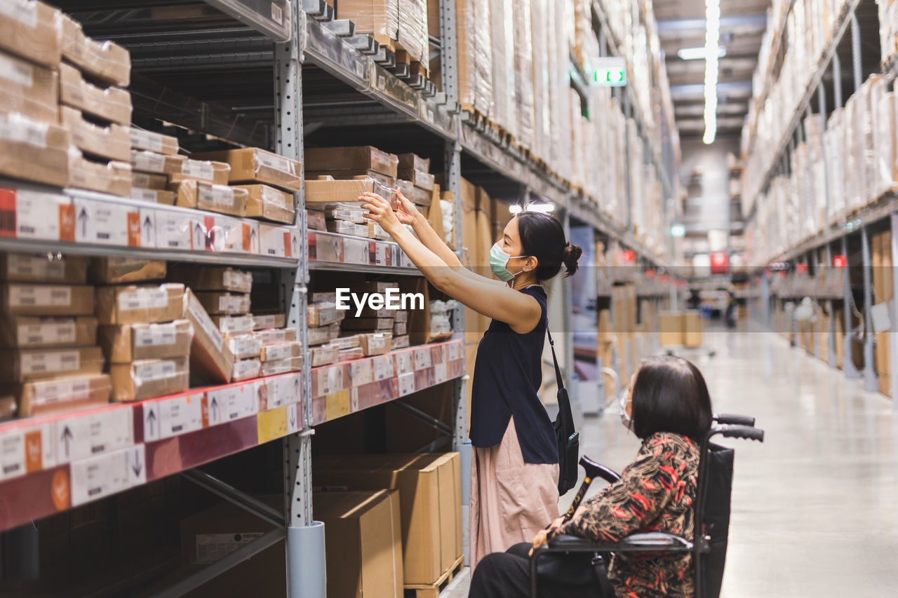 Woman in protective mask hand reaching box in warehouse interior shelves