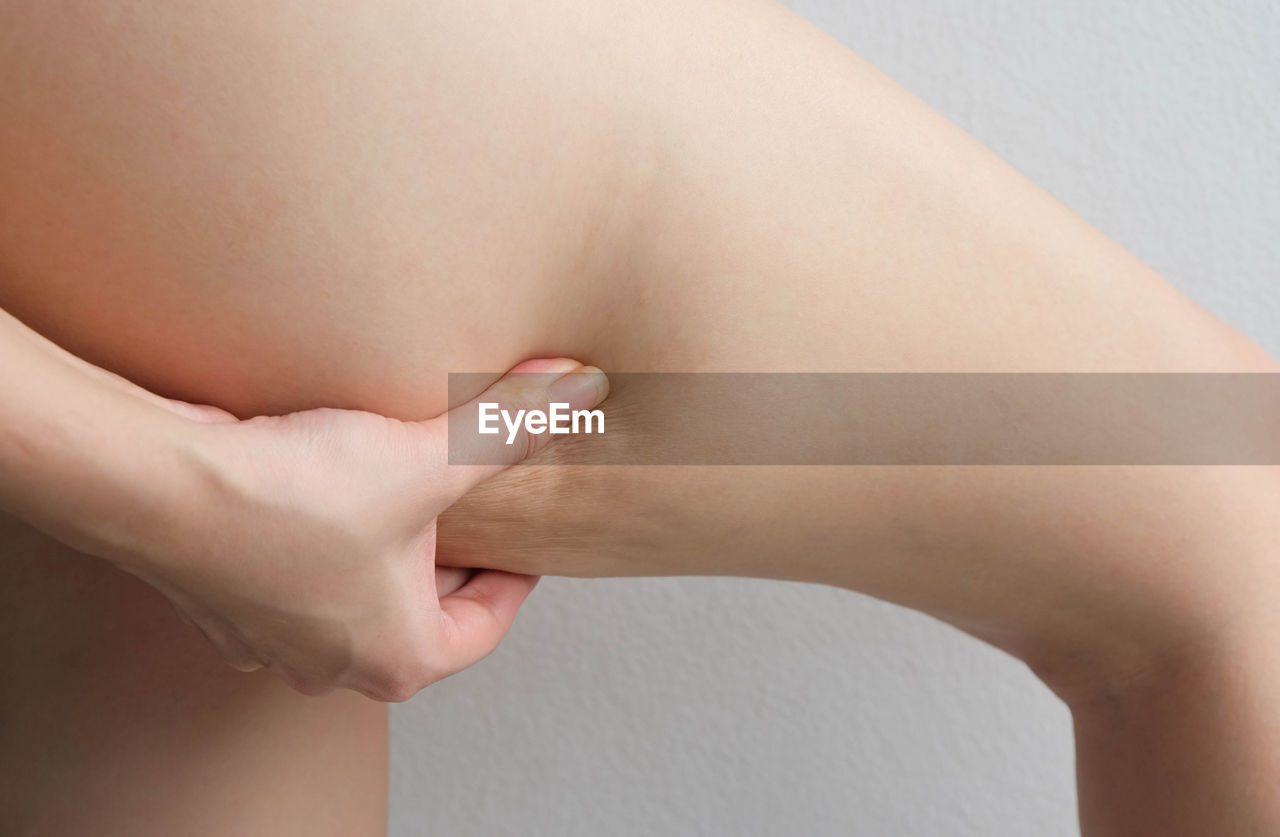 Cropped image of woman pinching thigh