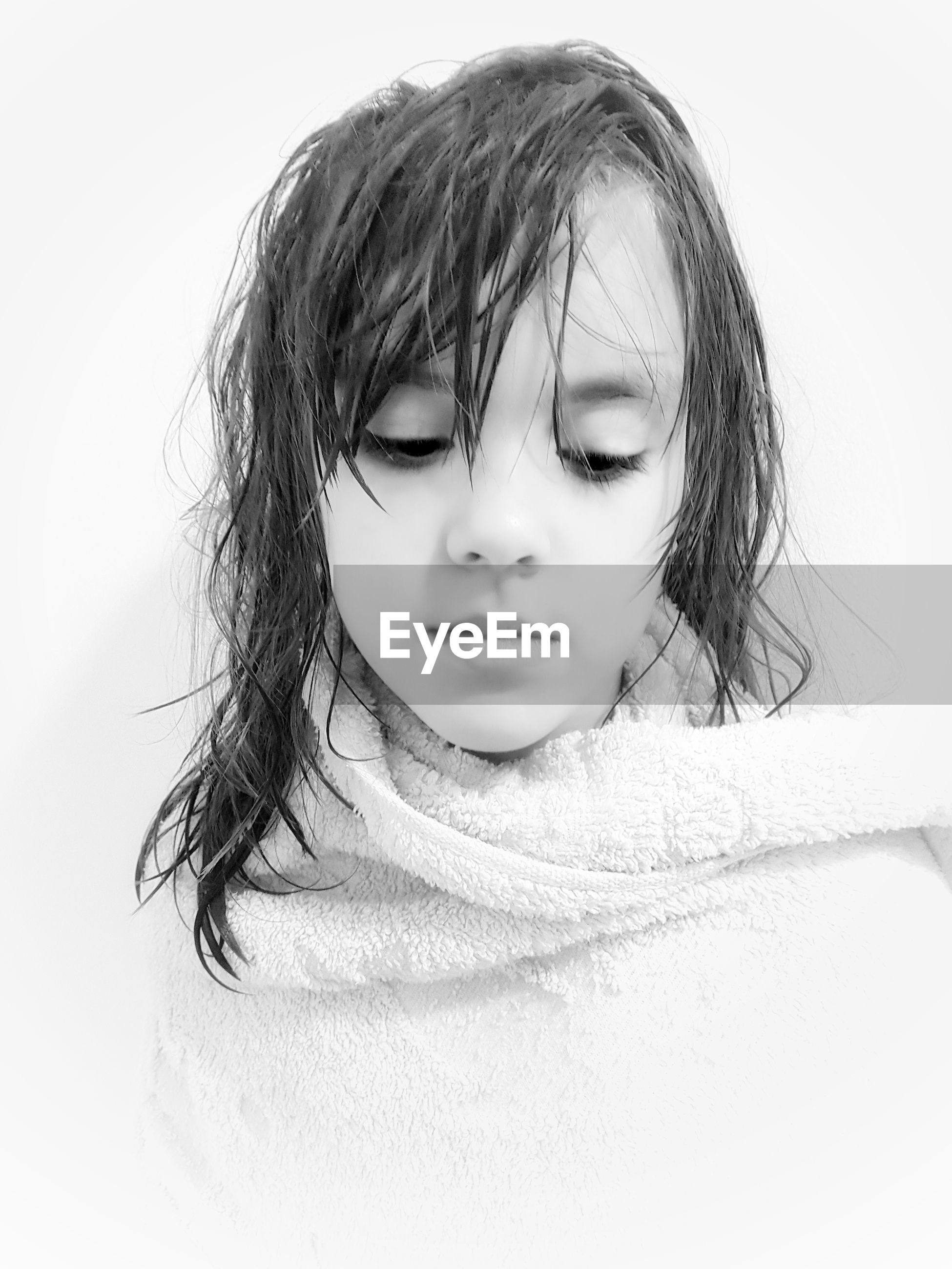 Close-up of girl wrapped in towel against white background
