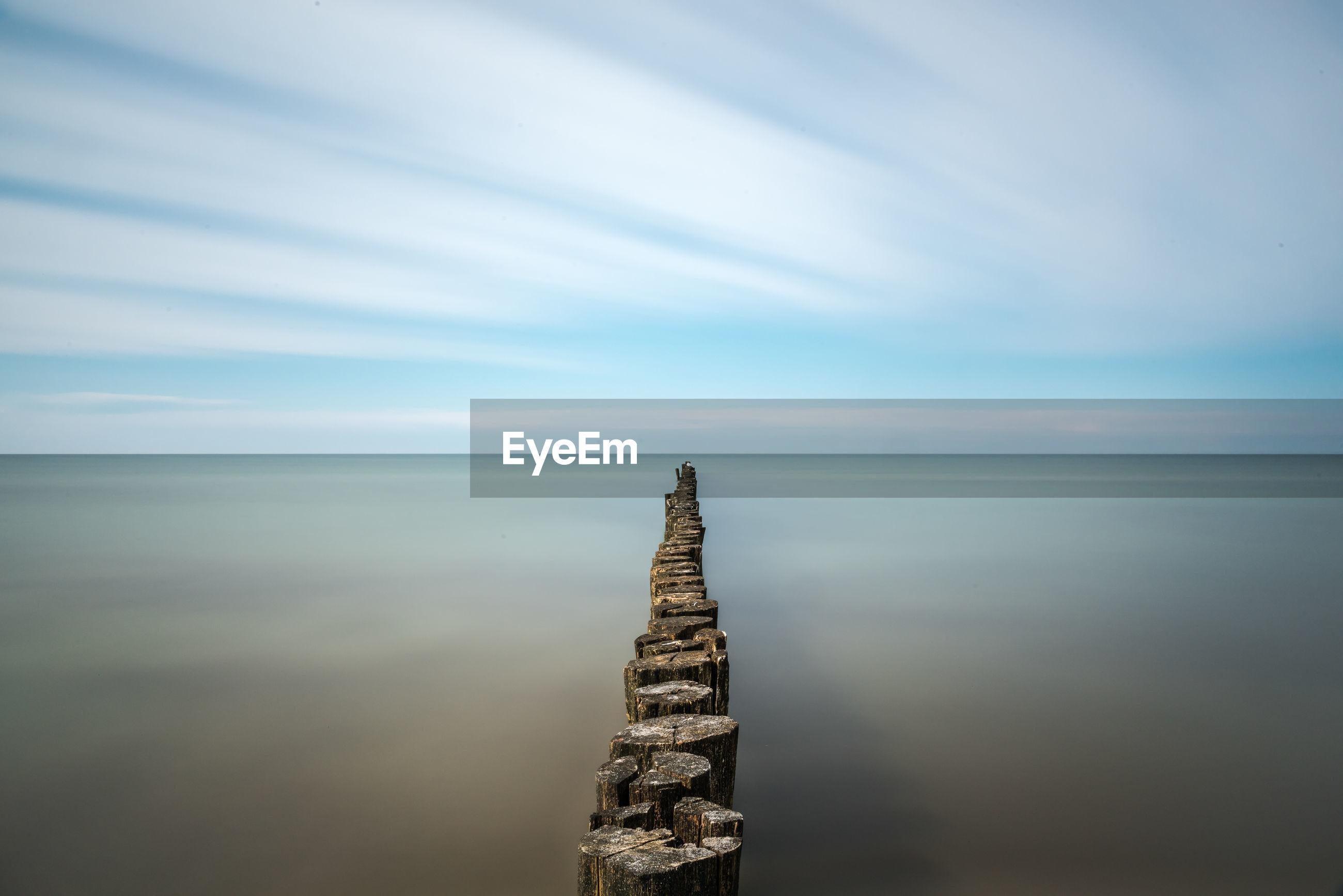 Groyne in sea against sky