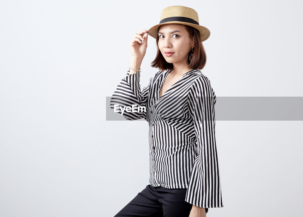 striped, hat, clothing, standing, studio shot, white background, one person, young adult, indoors, three quarter length, young women, copy space, casual clothing, lifestyles, looking, leisure activity, front view, cut out, beautiful woman, hairstyle