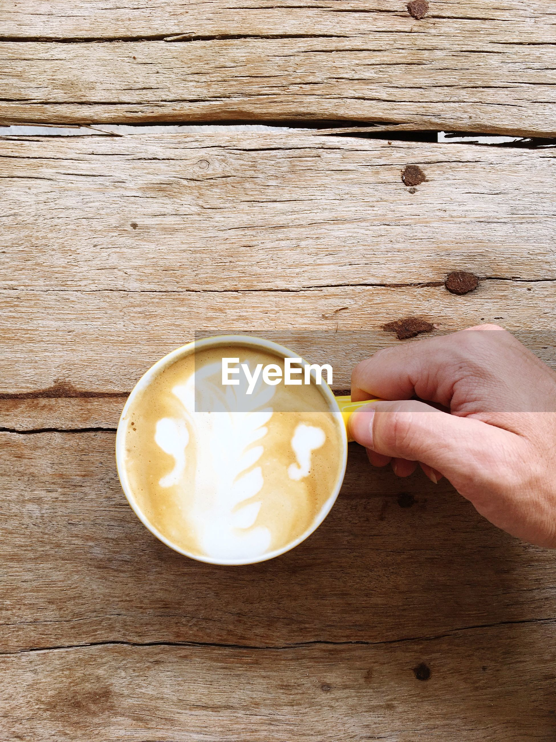 Cropped hand of man having coffee on table