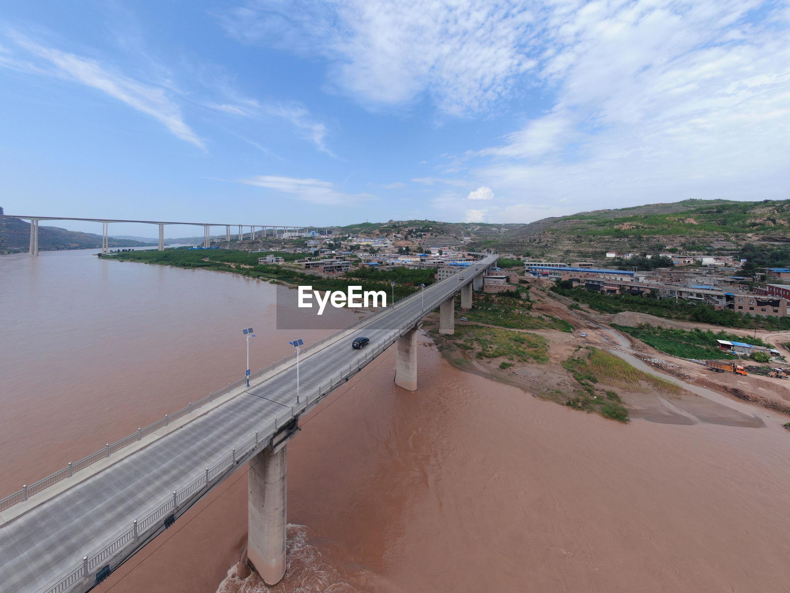 PANORAMIC VIEW OF BRIDGE OVER ROAD AGAINST SKY
