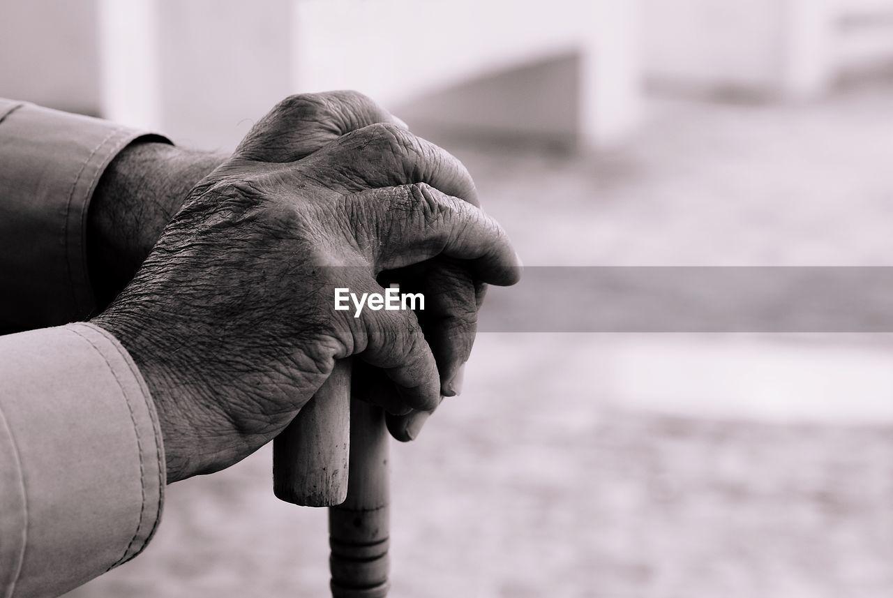 Cropped Hands Of Senior Man Holding Walking Cane