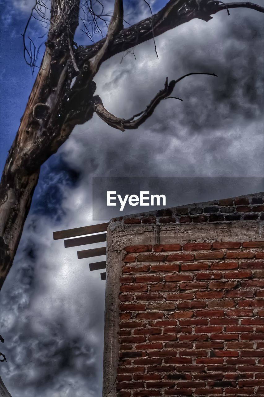 cloud - sky, sky, low angle view, built structure, architecture, building exterior, brick, nature, no people, brick wall, wall, day, tree, overcast, outdoors, bare tree, plant, branch, building, ominous