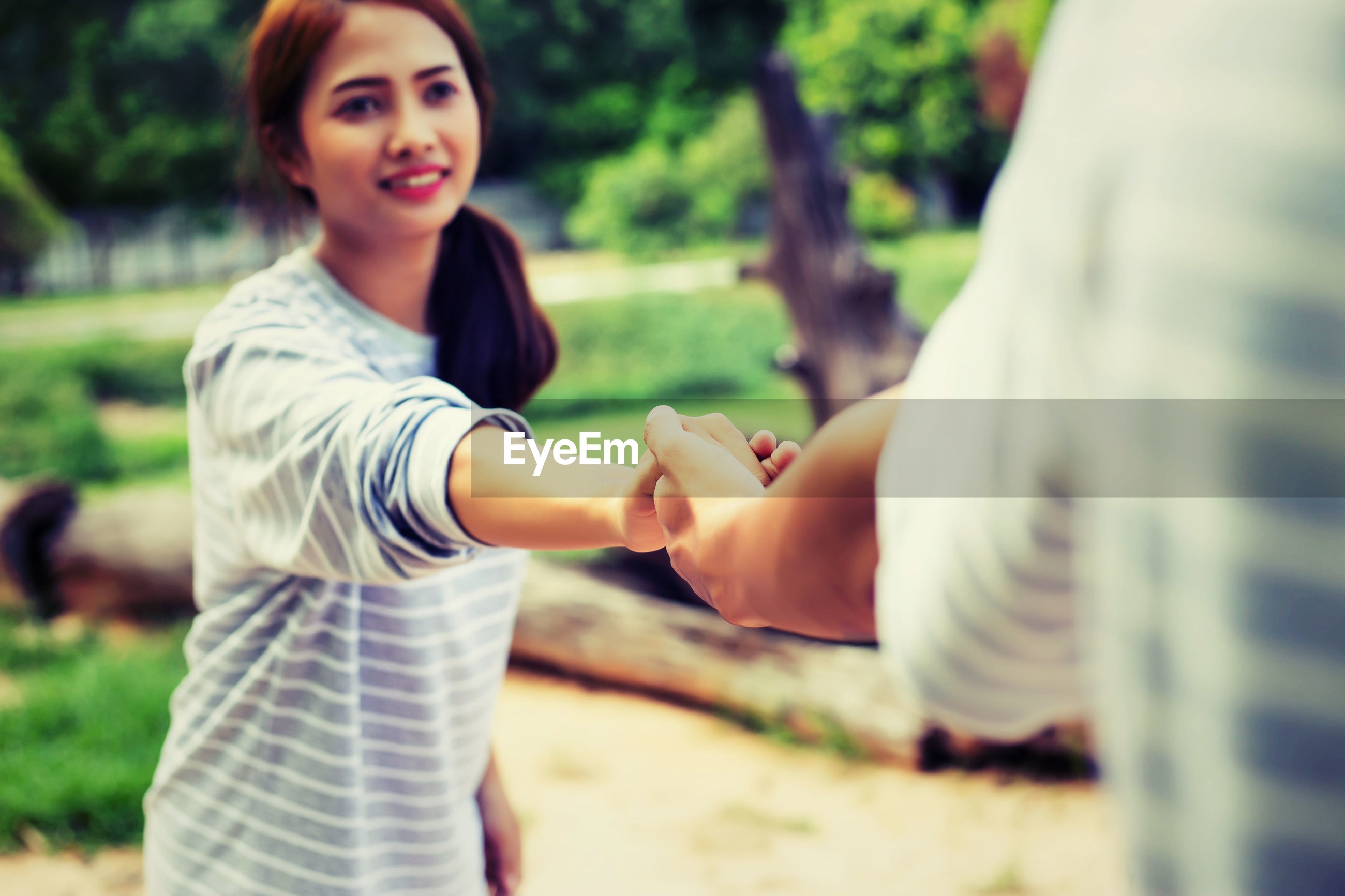 Smiling young woman holding hand of man