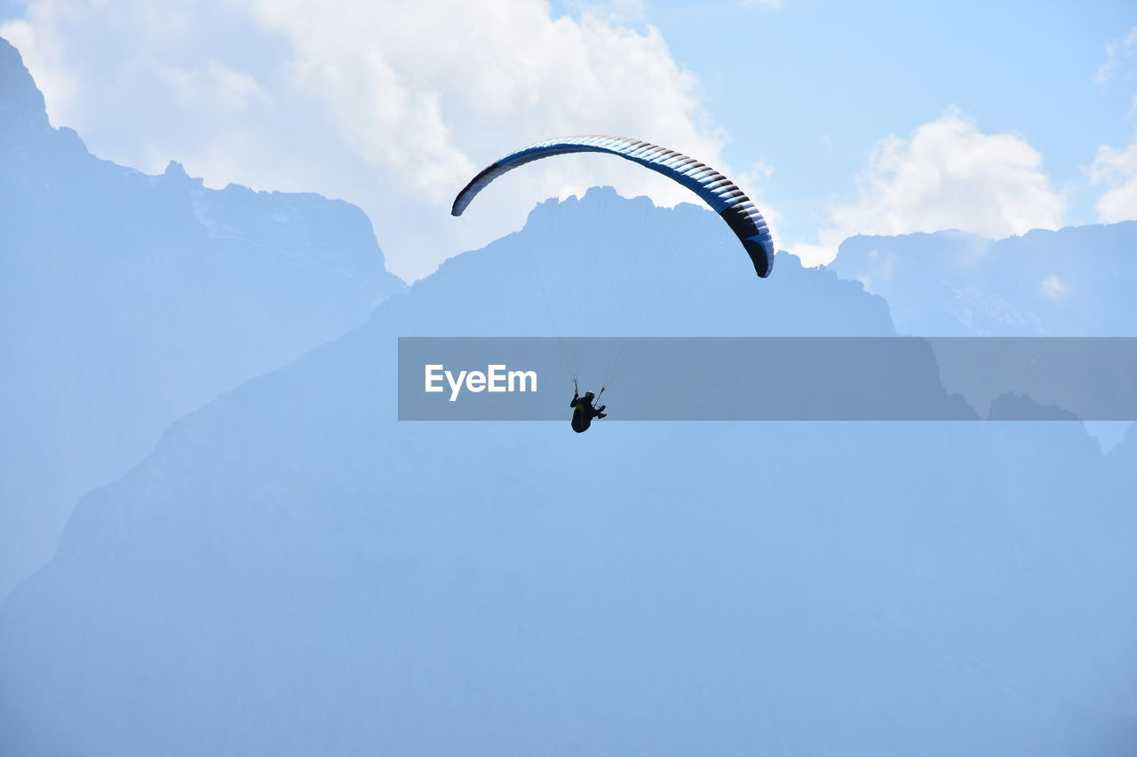 Low Angle View Of Person Paragliding Against Mountains