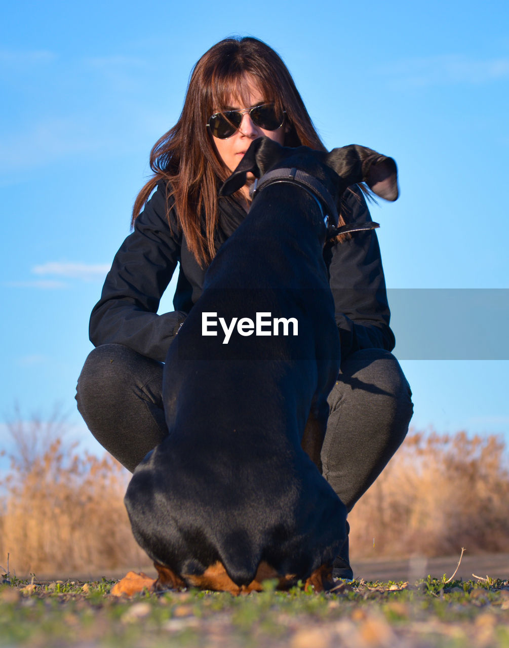 LOW ANGLE VIEW OF YOUNG WOMAN ON SUNGLASSES AGAINST SKY