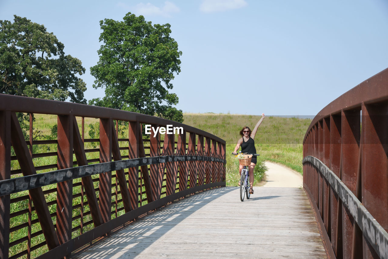 Full length of mature woman riding bicycle on footbridge against blue sky during sunny day