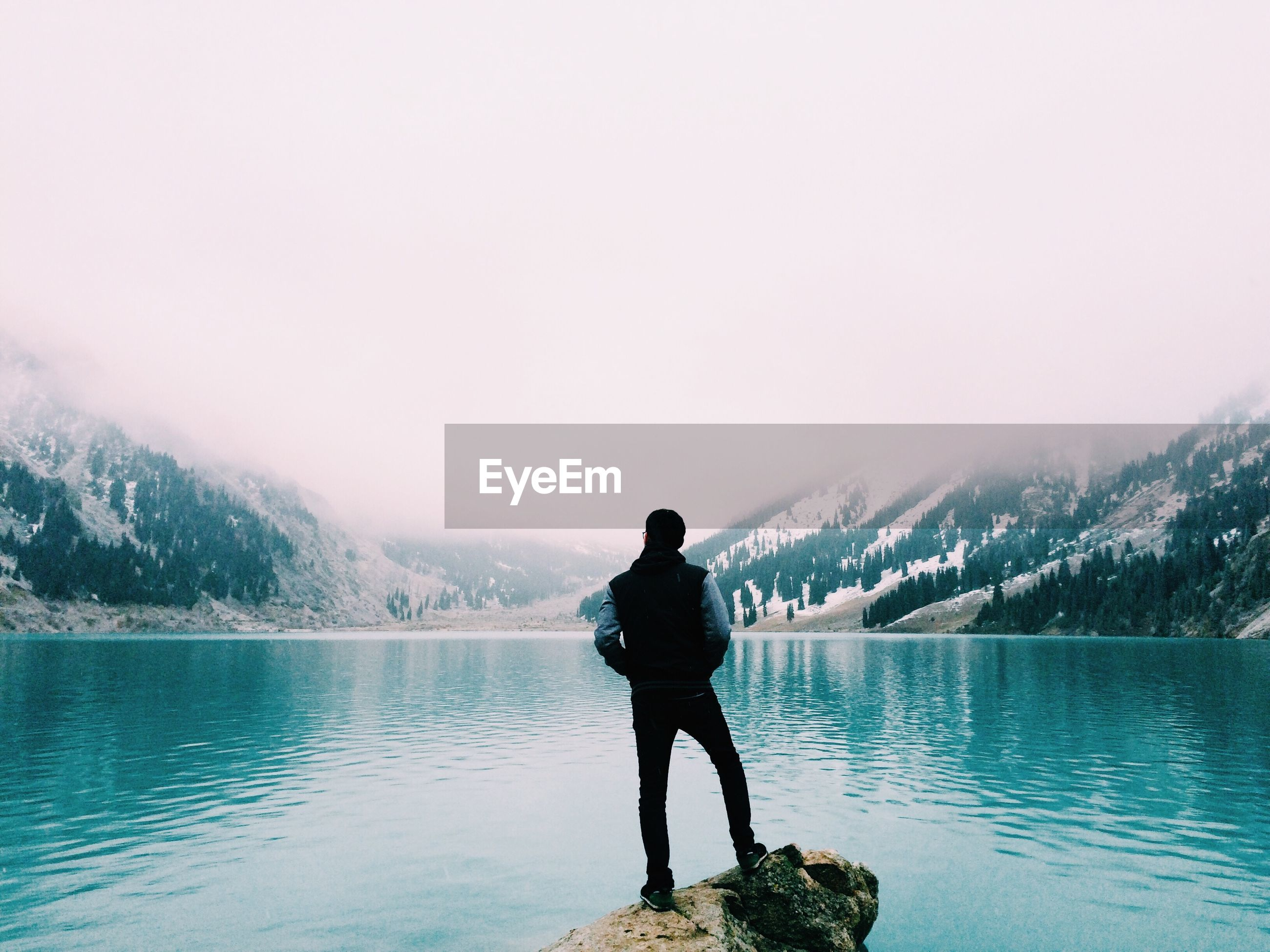 Rear view of man standing on rock over lake against mountain range