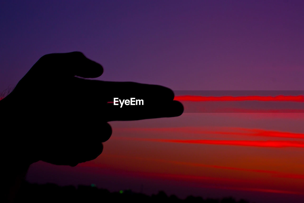 Close-up of silhouette hand gesturing gun sign against red sky during sunset