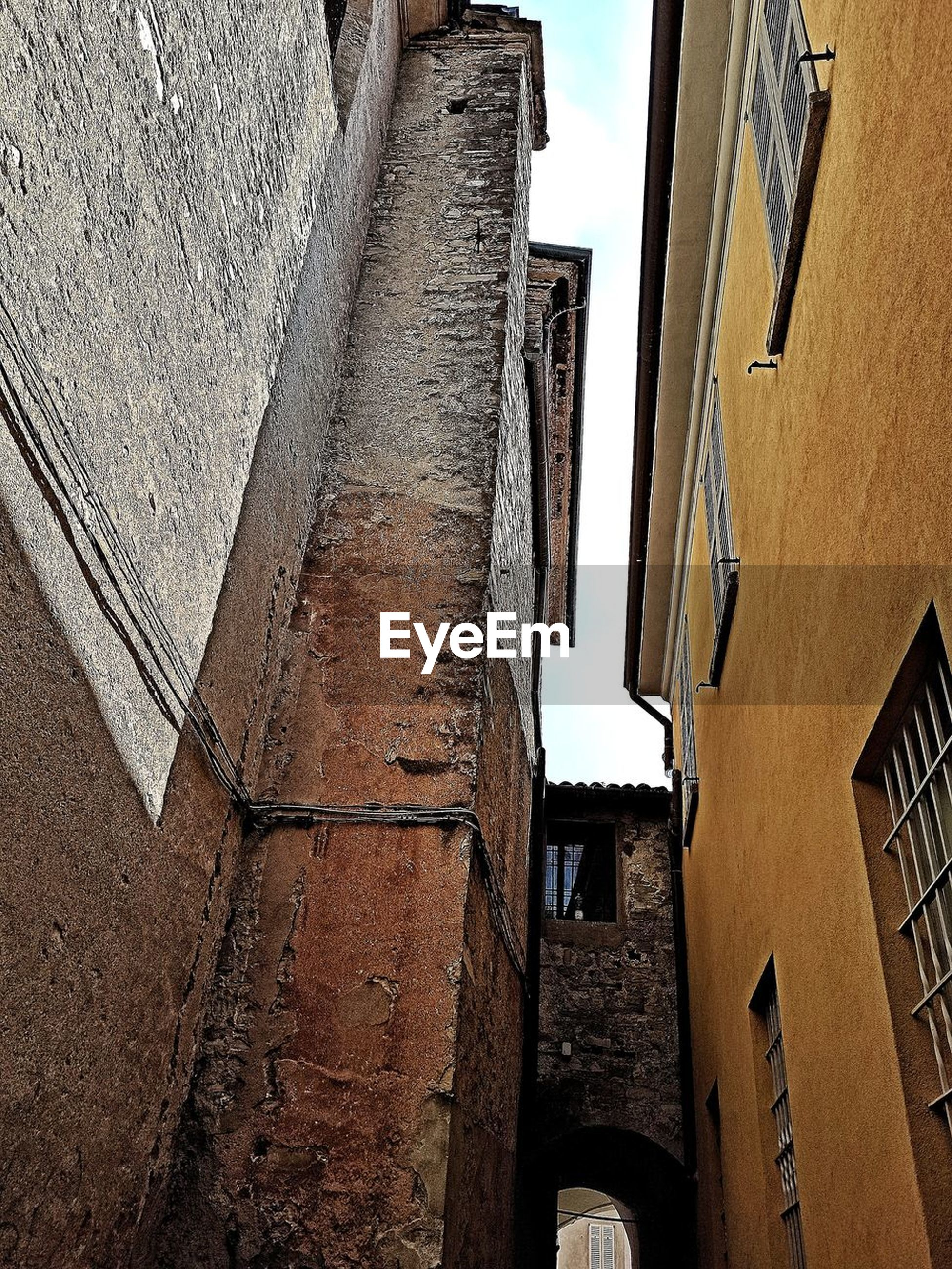 architecture, built structure, building exterior, wall, road, building, alley, low angle view, street, no people, wall - building feature, window, residential district, city, day, infrastructure, urban area, house, nature, outdoors, sky, black, old