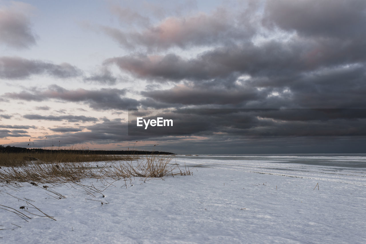 SCENIC VIEW OF SEA AGAINST SNOW COVERED LAND