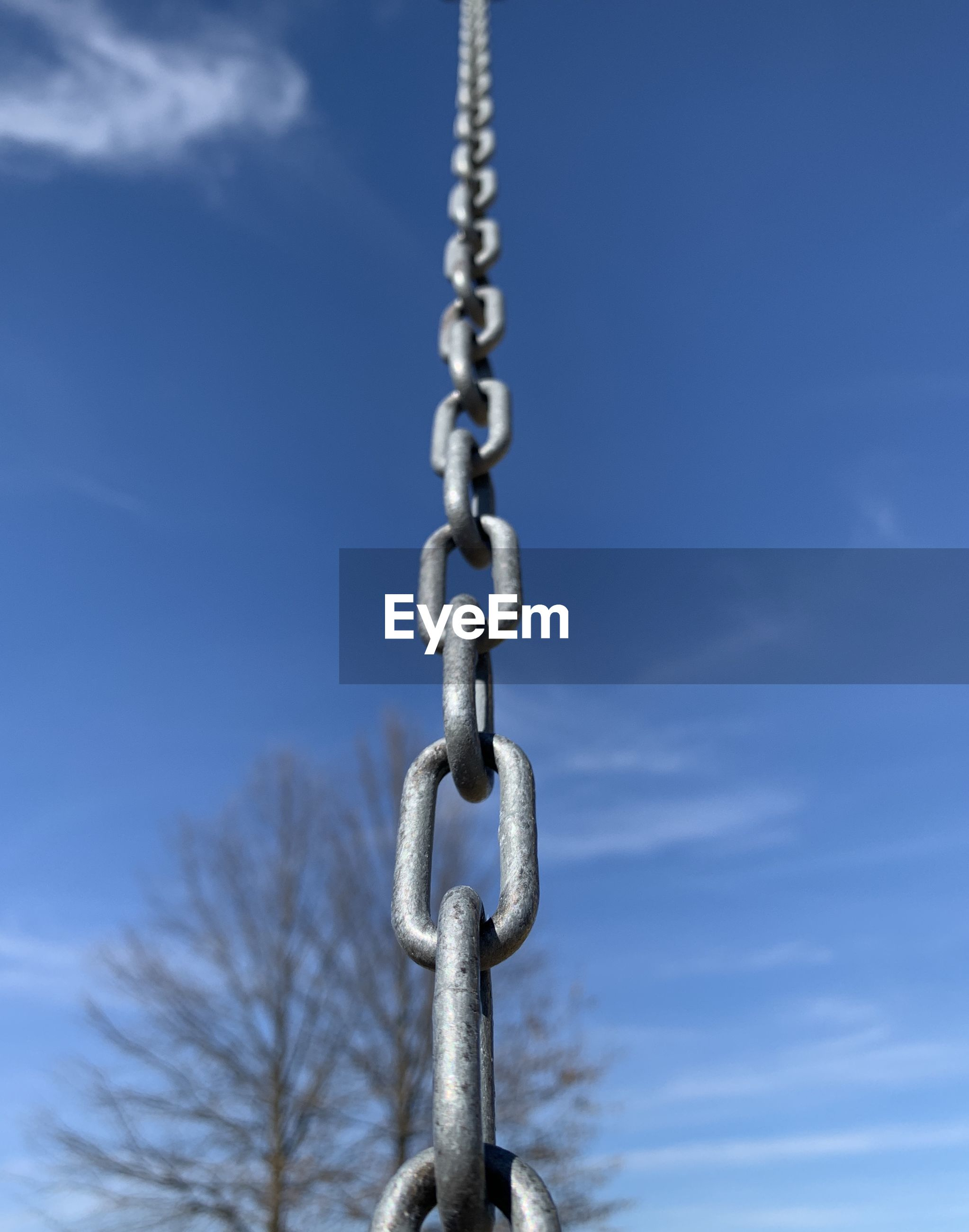 CLOSE-UP OF CHAIN AGAINST BLUE SKY