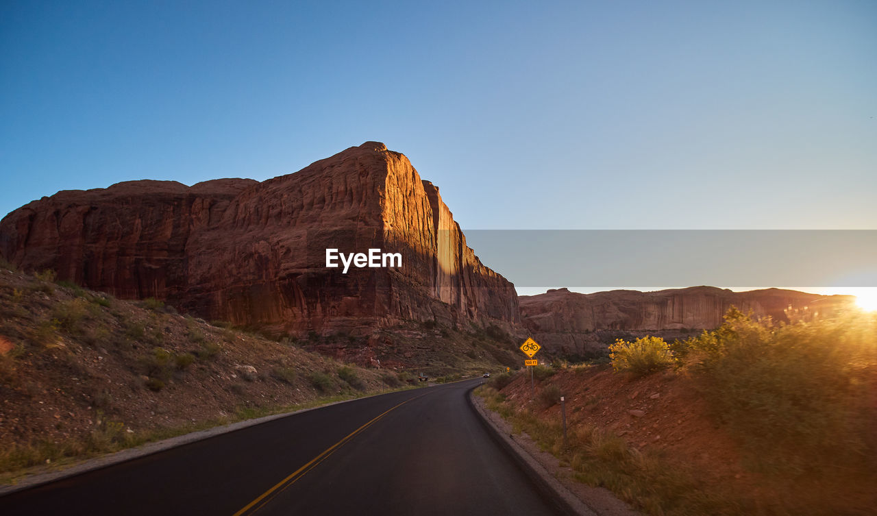 sky, road, mountain, clear sky, nature, direction, transportation, the way forward, no people, beauty in nature, non-urban scene, tranquil scene, scenics - nature, copy space, rock, tranquility, mountain range, symbol, rock formation, landscape, diminishing perspective, outdoors, formation