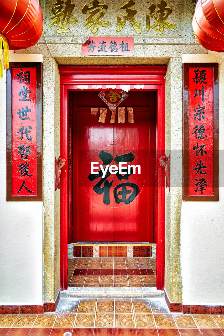 TEXT ON RED DOOR OF BUILDING WITH CLOSED DOORS