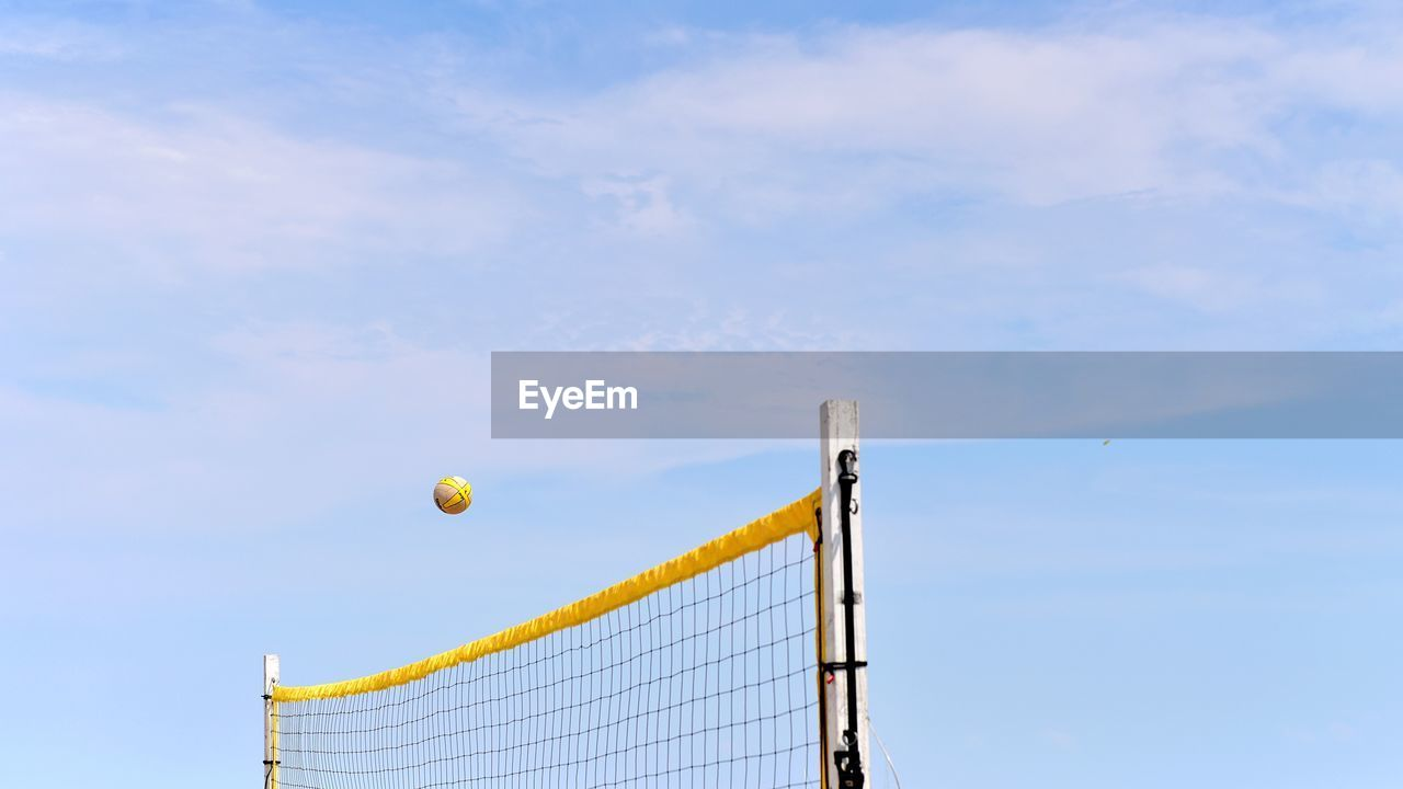 Volleyball in air over volleyball net