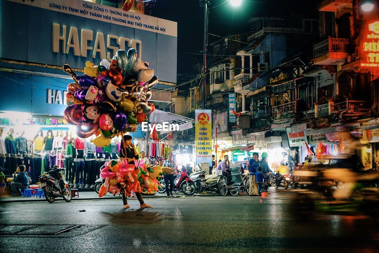 night, illuminated, street, transportation, real people, city life, large group of people, city, architecture, store, building exterior, built structure, lifestyles, outdoors, men, women, crowd, people