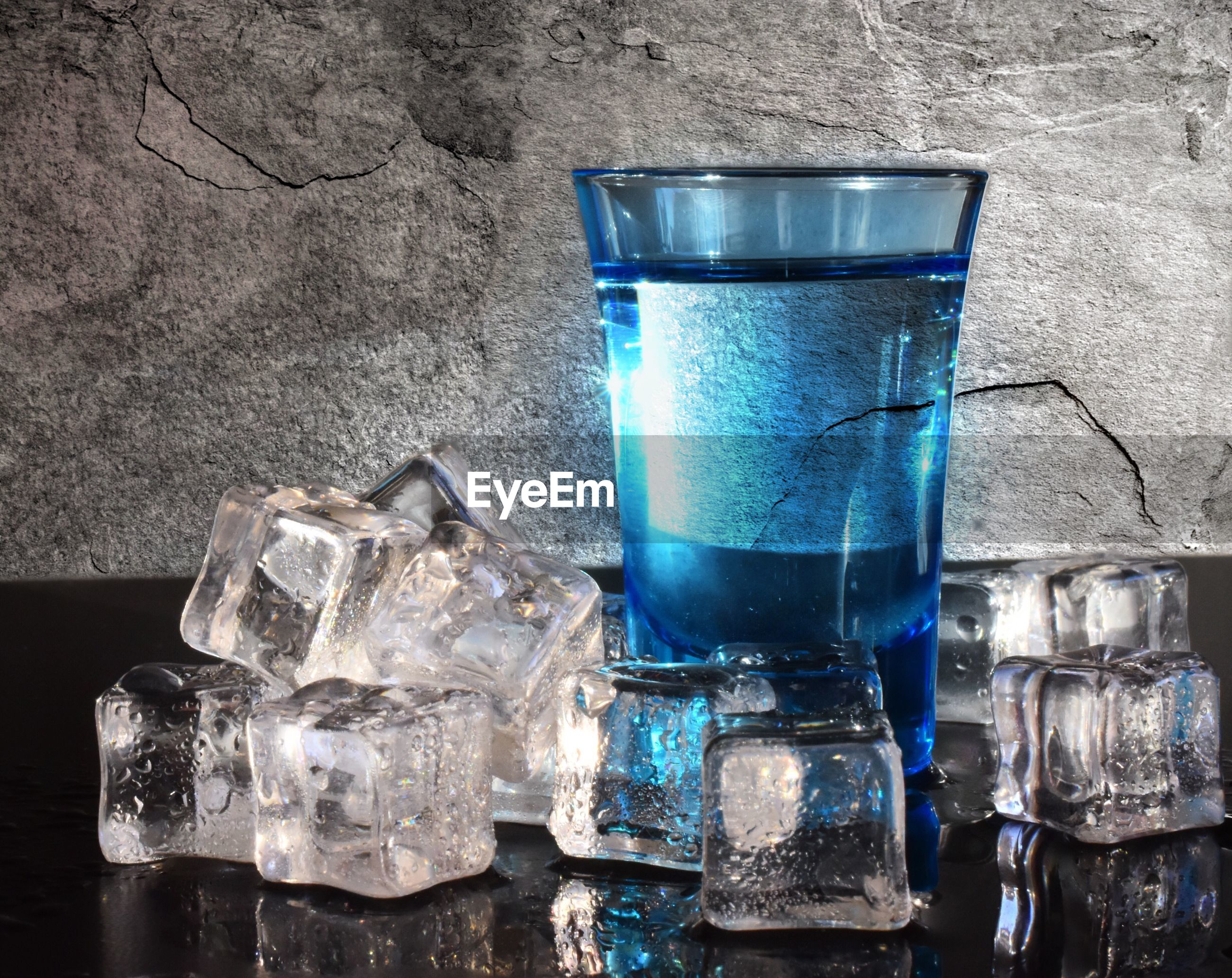 Close-up of glass of water with ice cubs on table against wall