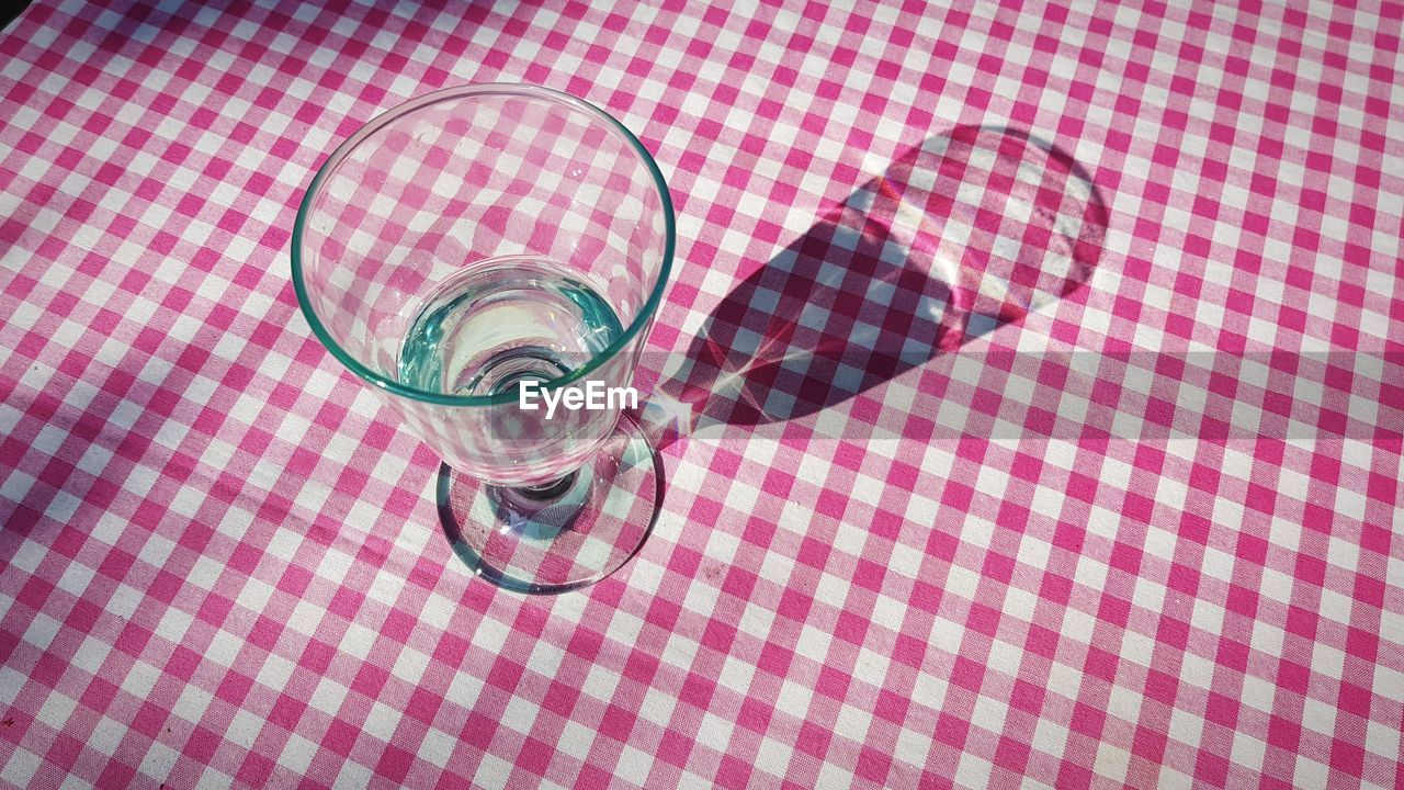 HIGH ANGLE VIEW OF DRINK ON GLASS TABLE