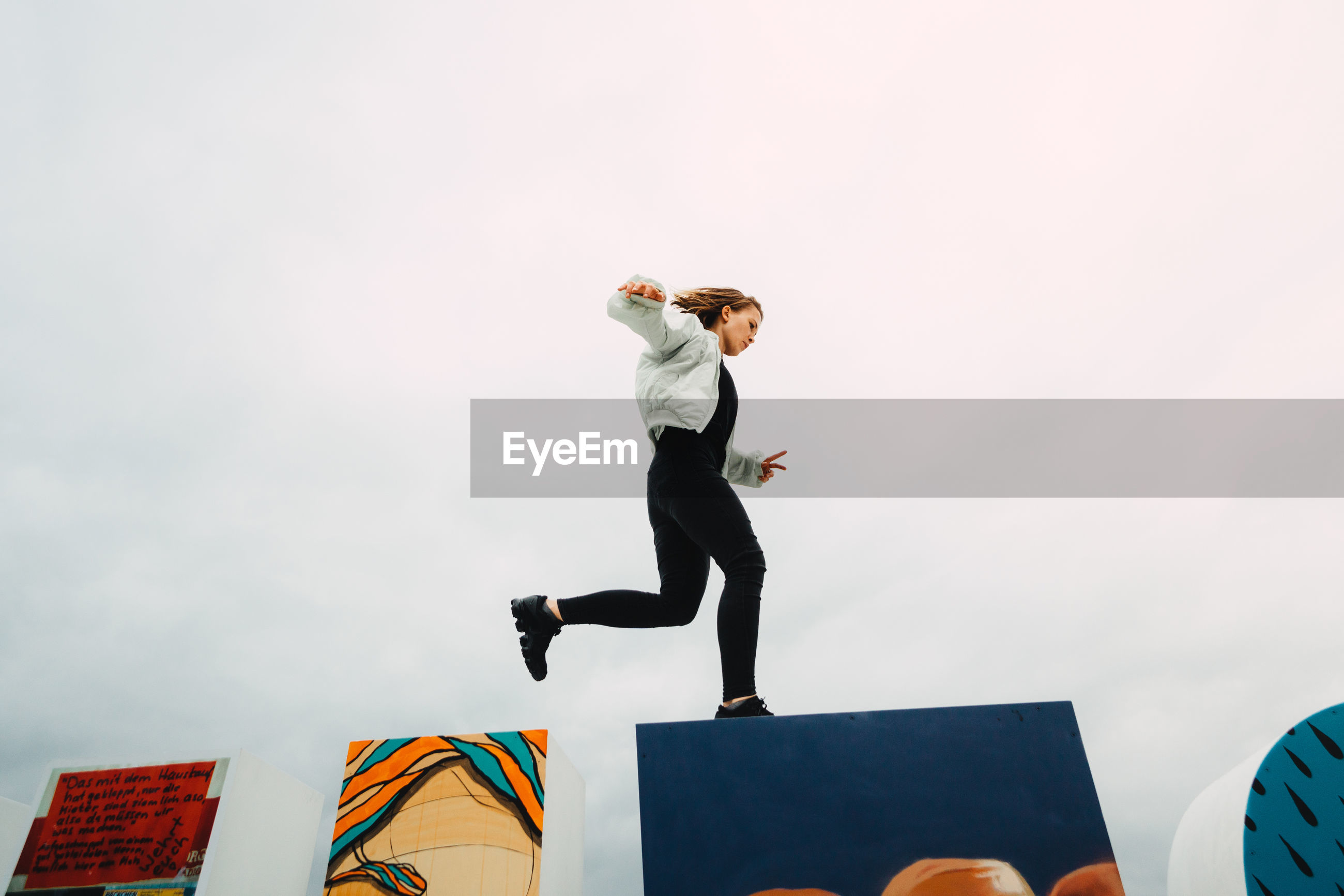 Low angle view of woman jumping over wall against sky