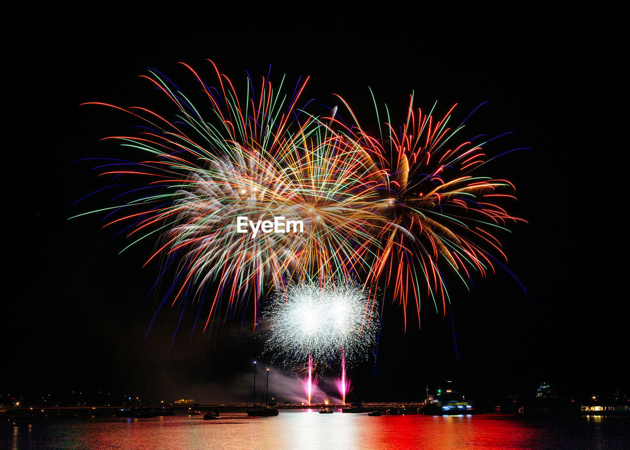 night, illuminated, firework, motion, celebration, firework display, exploding, event, arts culture and entertainment, long exposure, multi colored, sky, firework - man made object, glowing, nature, water, light, blurred motion, no people, sparks, outdoors
