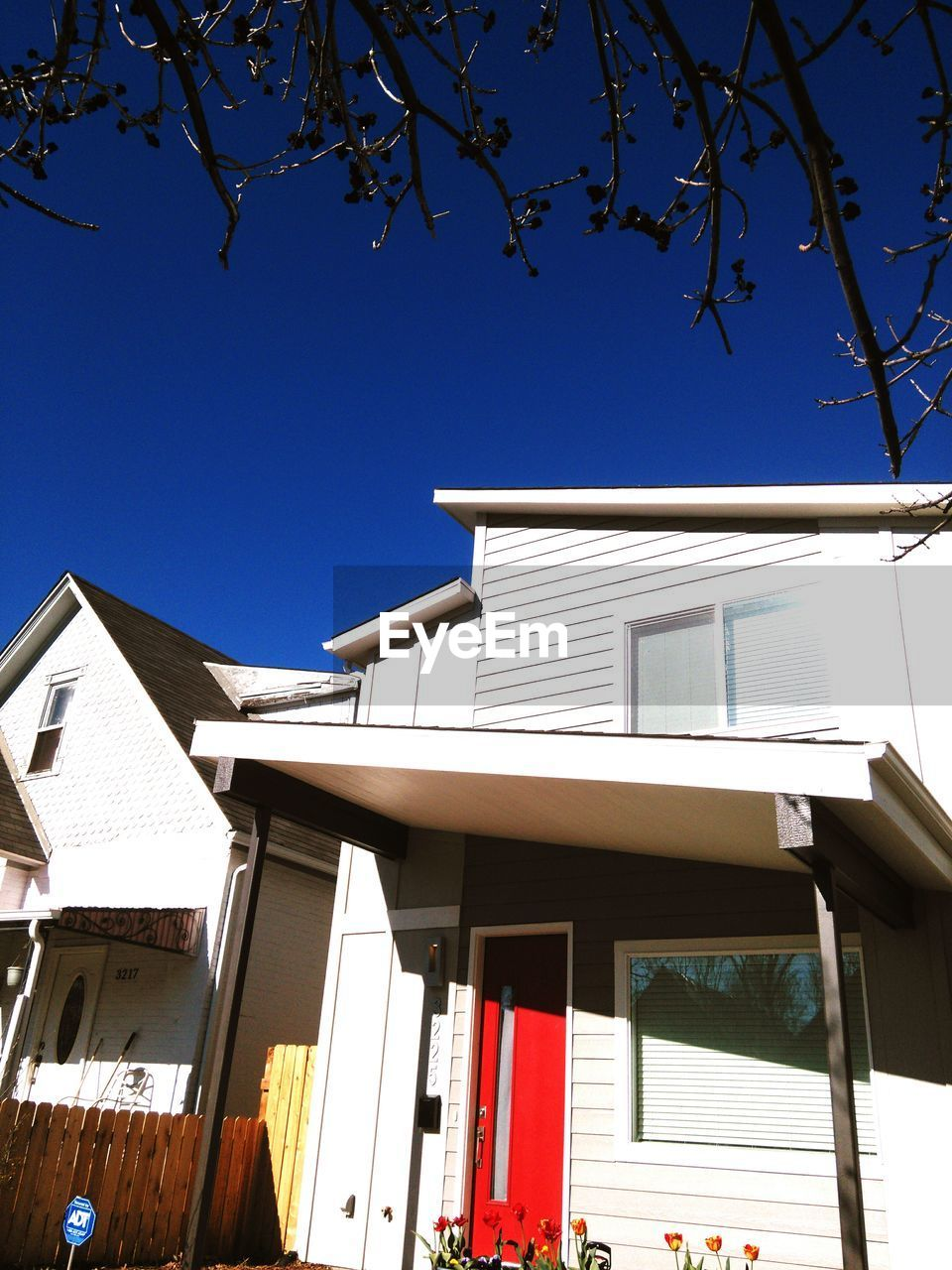 Low Angle View Of Houses Against Blue Sky On Sunny Day