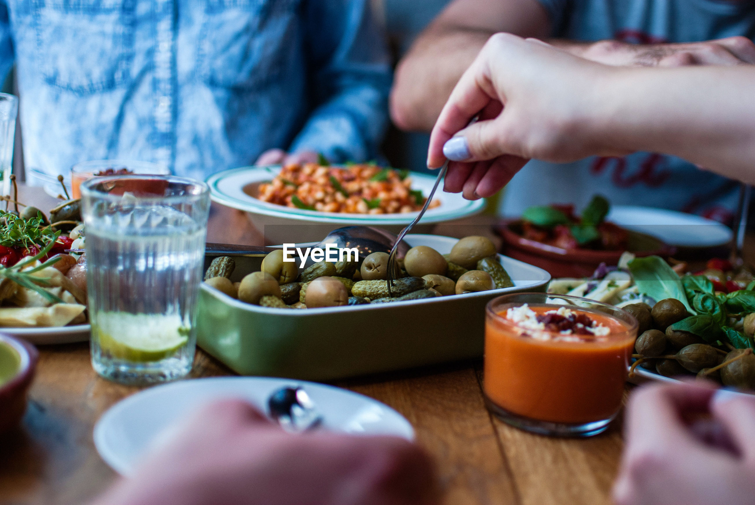 Cropped image of friends having lunch on table