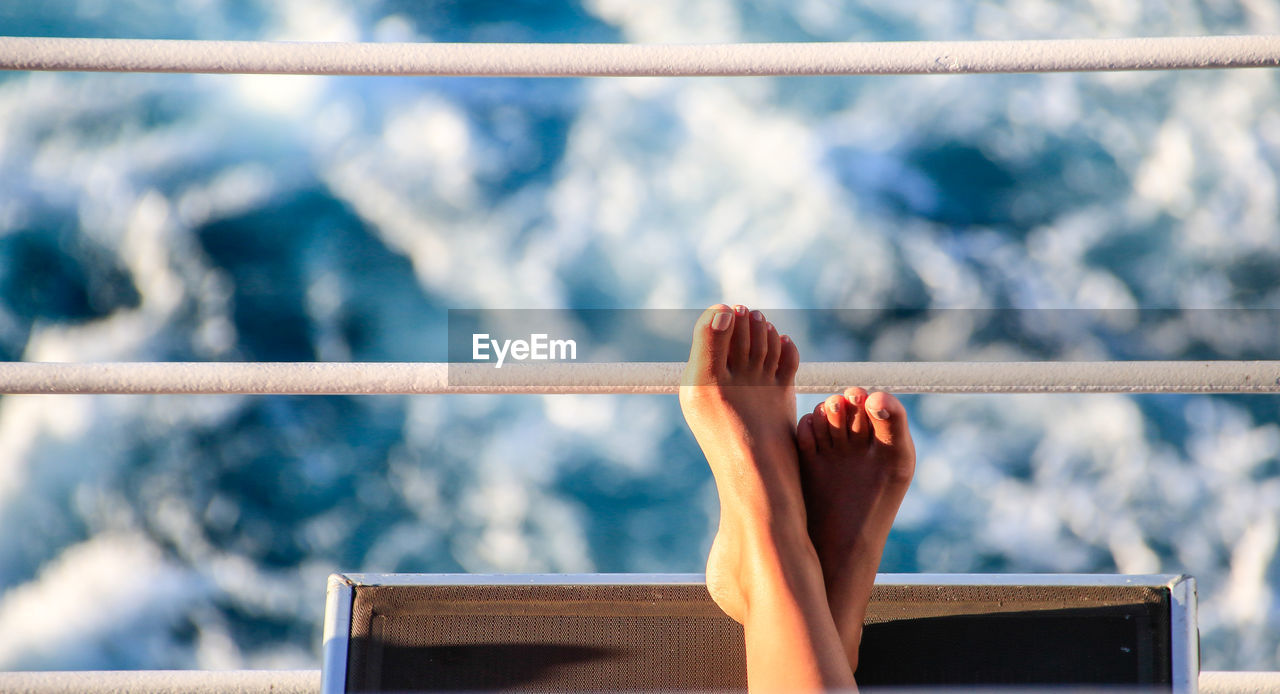 Low Section Of Woman Relaxing On Boat