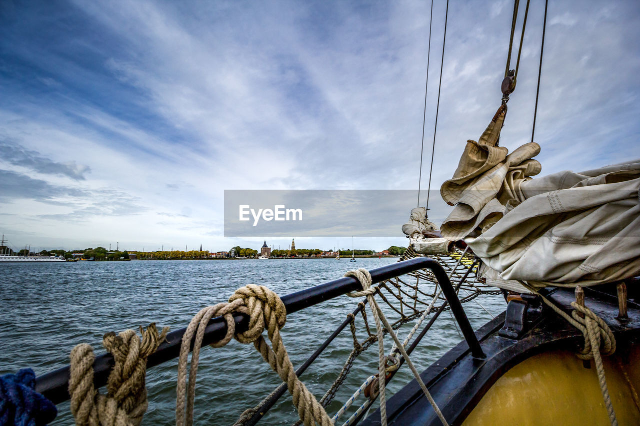 sky, water, nautical vessel, transportation, rope, cloud - sky, mode of transportation, nature, no people, day, outdoors, river, connection, tied up, tranquility, beauty in nature, strength, sailboat