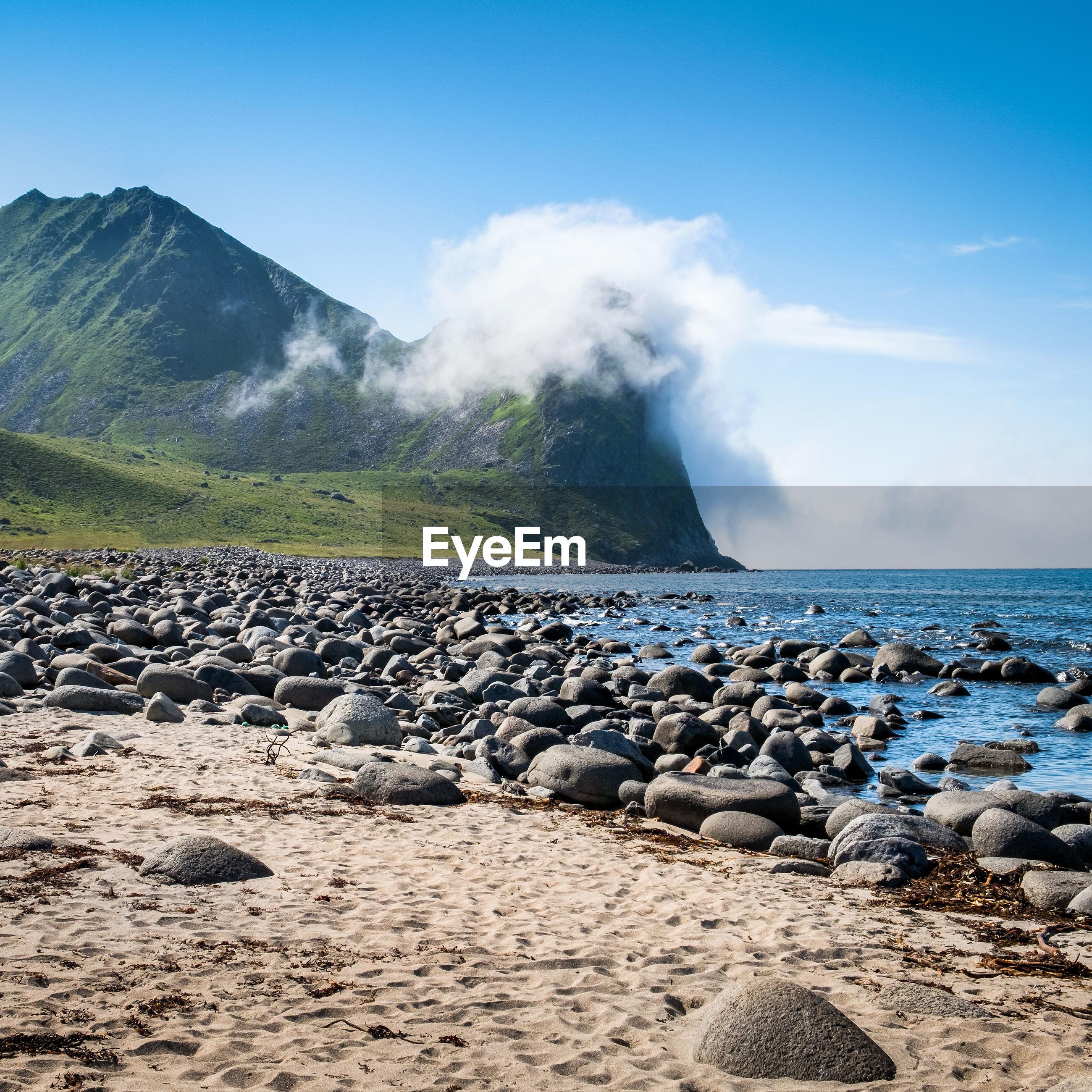 ROCKS AT SEA SHORE AGAINST SKY