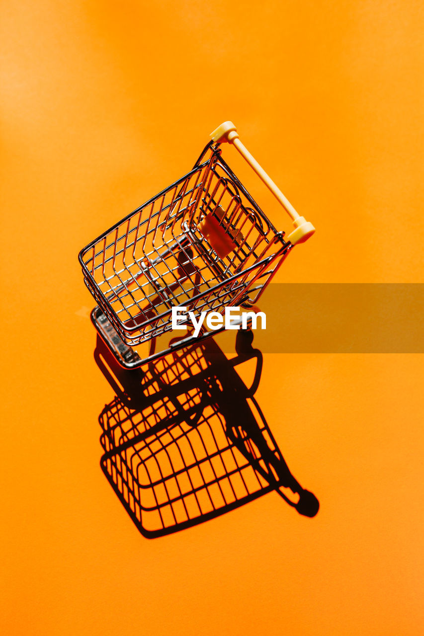 High angle view of small shopping cart on orange background
