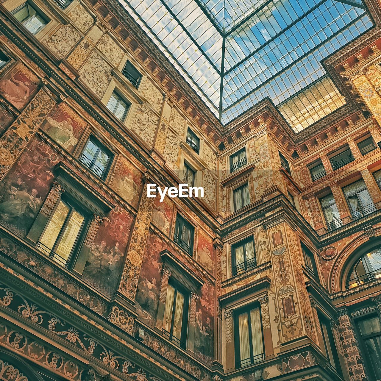 low angle view, built structure, architecture, building exterior, window, building, no people, day, glass - material, full frame, pattern, history, the past, outdoors, glass, city, design, reflection, sky, ceiling, ornate