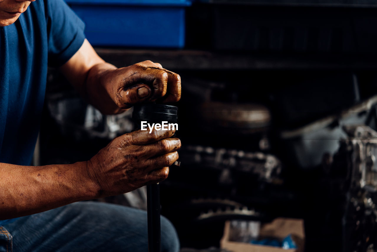 one person, human hand, men, occupation, real people, hand, holding, focus on foreground, indoors, working, human body part, midsection, repairing, skill, technician, business, auto repair shop, workshop, mechanic, finger, human limb