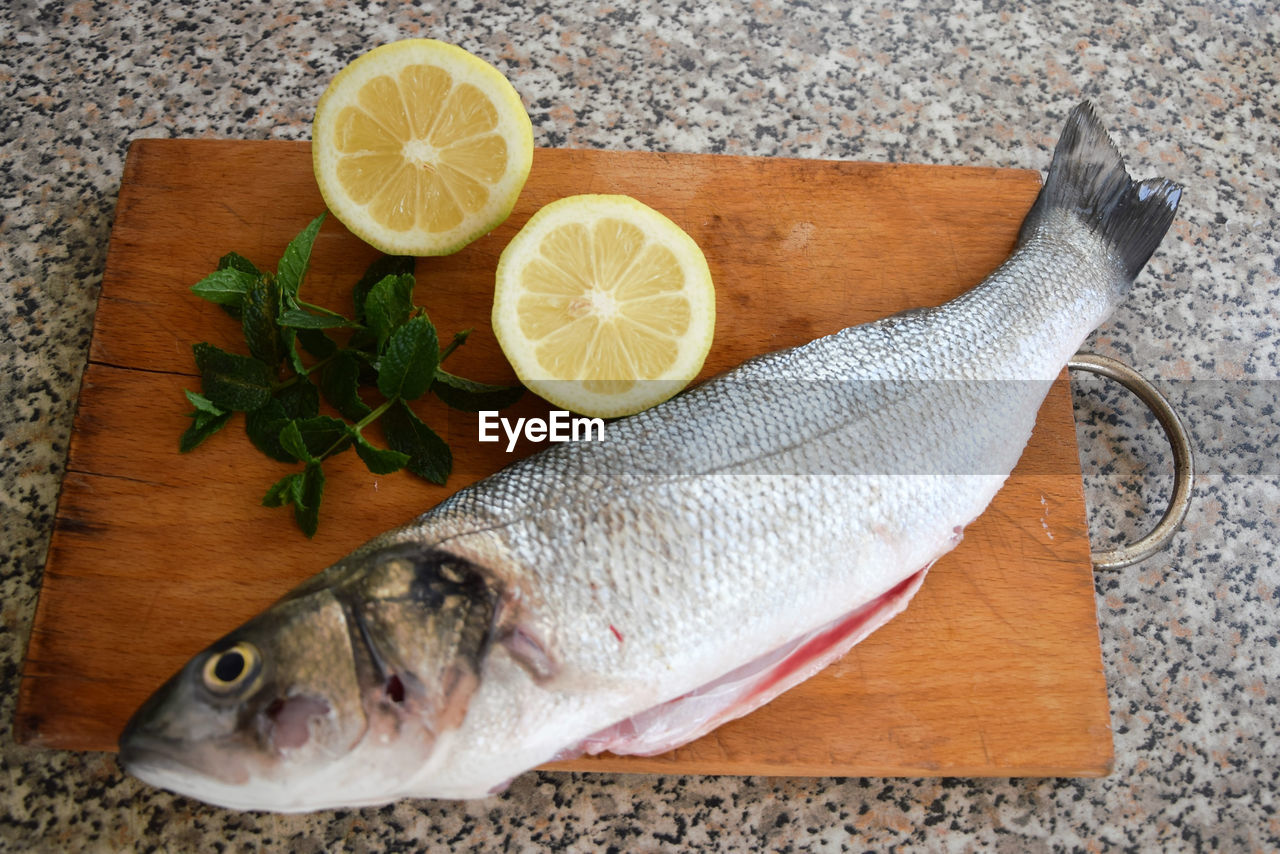 food, food and drink, freshness, citrus fruit, fish, healthy eating, lemon, vertebrate, wellbeing, seafood, animal, slice, fruit, indoors, no people, raw food, table, cutting board, still life, herb