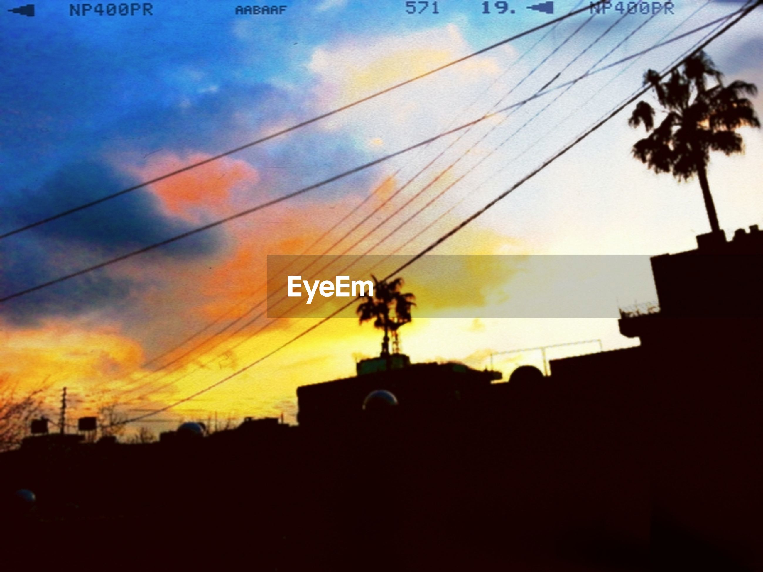 silhouette, low angle view, sunset, architecture, built structure, building exterior, power line, sky, cable, street light, dusk, electricity, cloud - sky, orange color, no people, lighting equipment, outdoors, building, power supply, electricity pylon