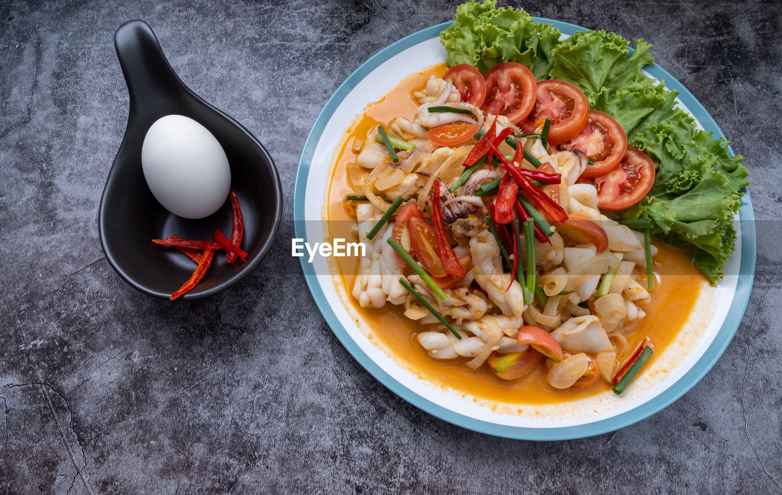 Stir-fried squid with salted egg yolk, onion, spring onion and chili pepper on white plate.