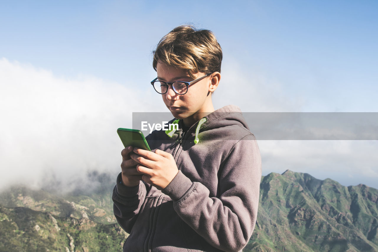 Boy using mobile phone while standing against mountain range