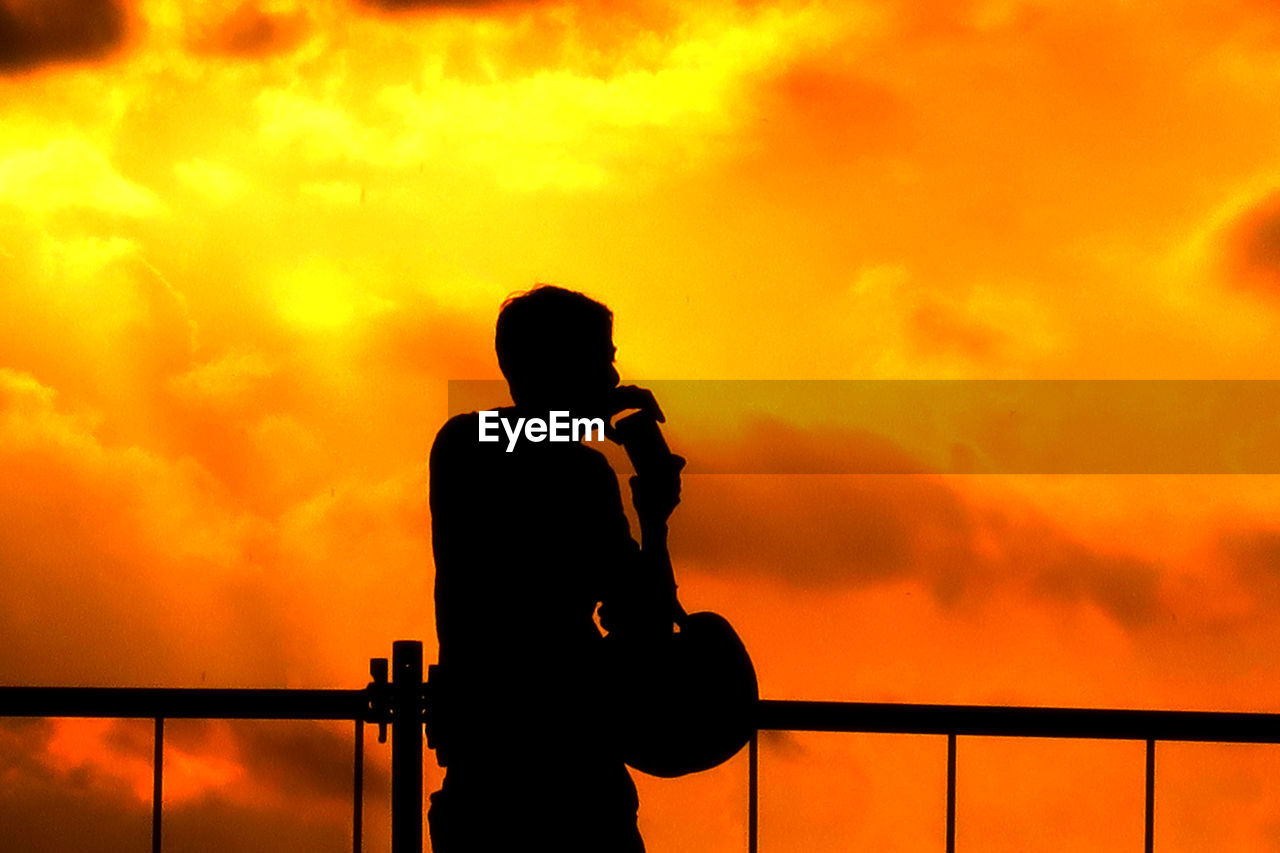Silhouette Of Person Photographing Orange Sky