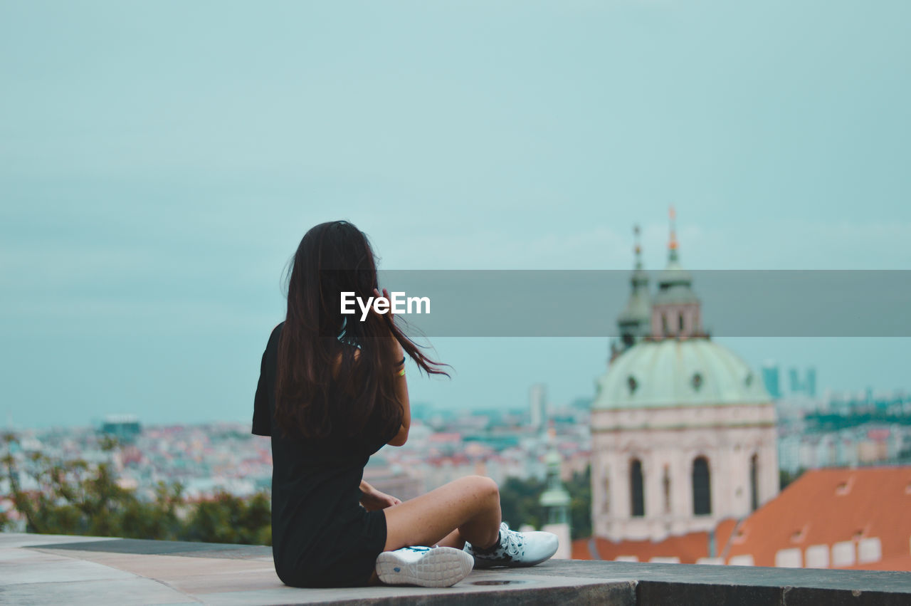 Woman Sitting Against Sky In City