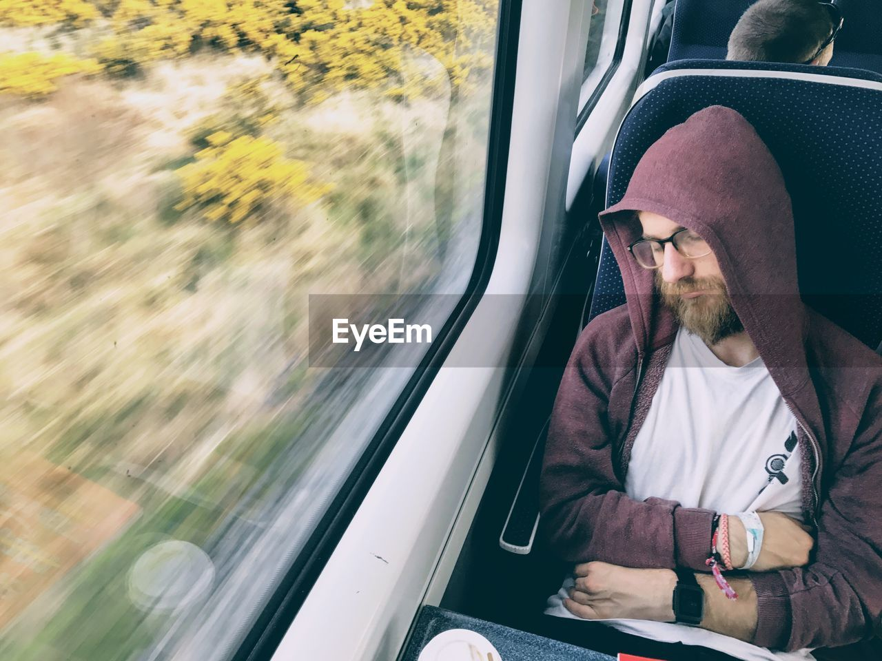 High Angle View Of Man Sleeping While Traveling In Train