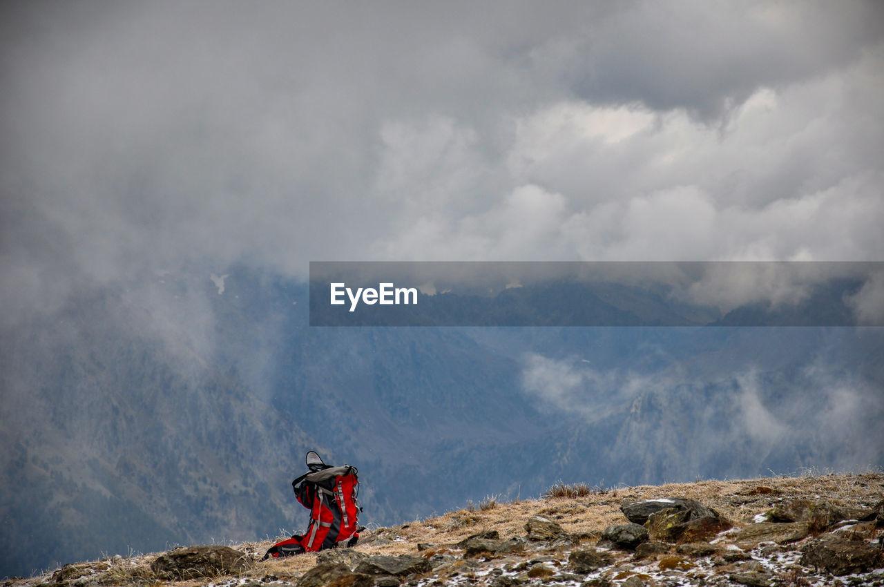 Backpack On Mountain Peak Against Cloudy Sky