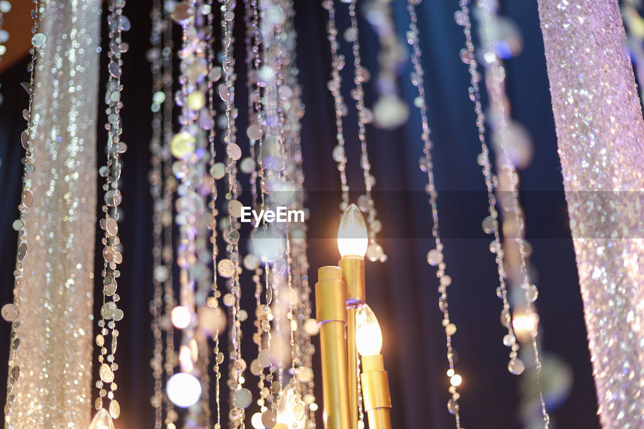 illuminated, no people, hanging, close-up, decoration, selective focus, focus on foreground, lighting equipment, crystal, glowing, nature, outdoors, night, celebration, built structure, candle, large group of objects, burning, purple