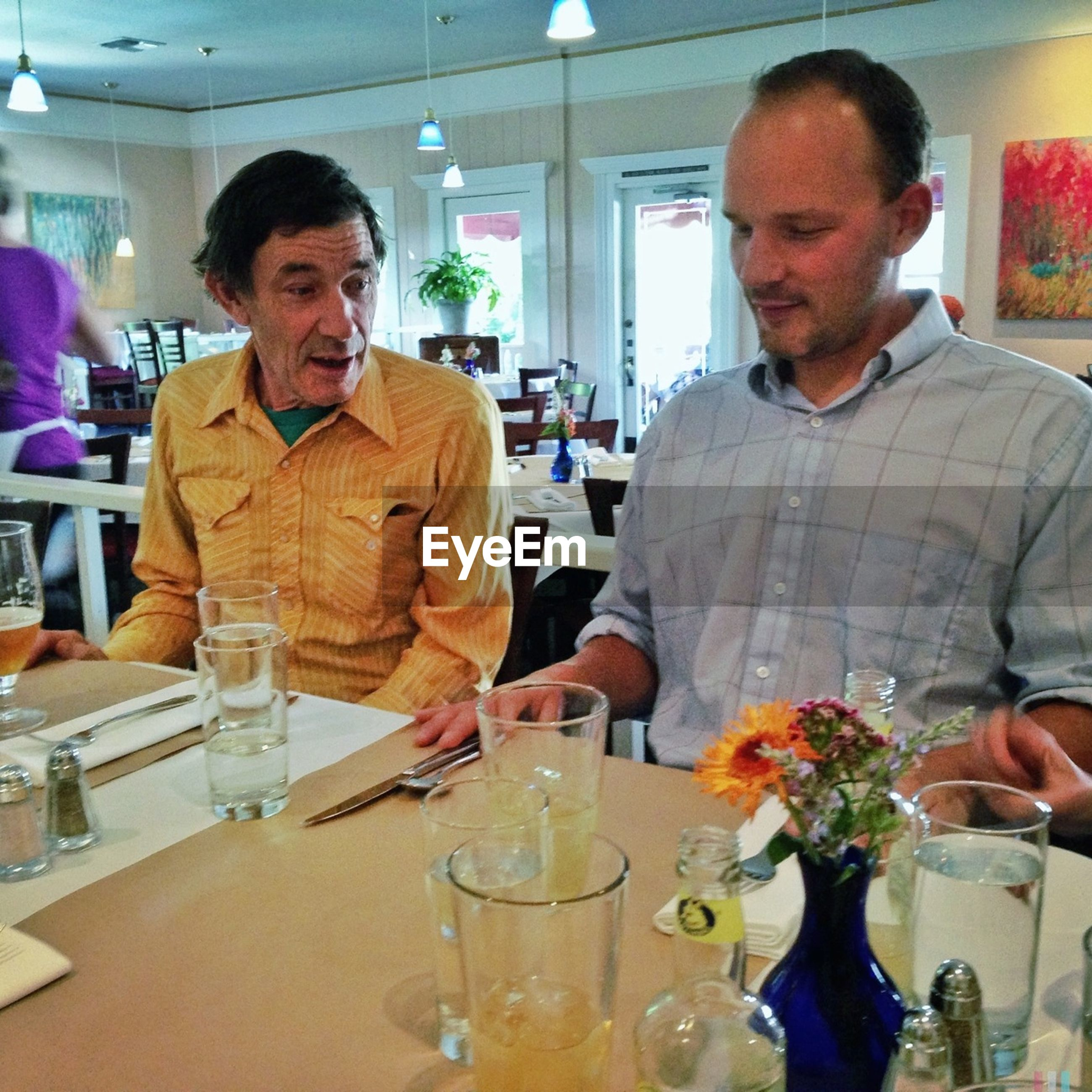 indoors, food and drink, lifestyles, person, young men, casual clothing, drink, young adult, leisure activity, restaurant, front view, holding, sitting, table, refreshment, drinking glass, incidental people