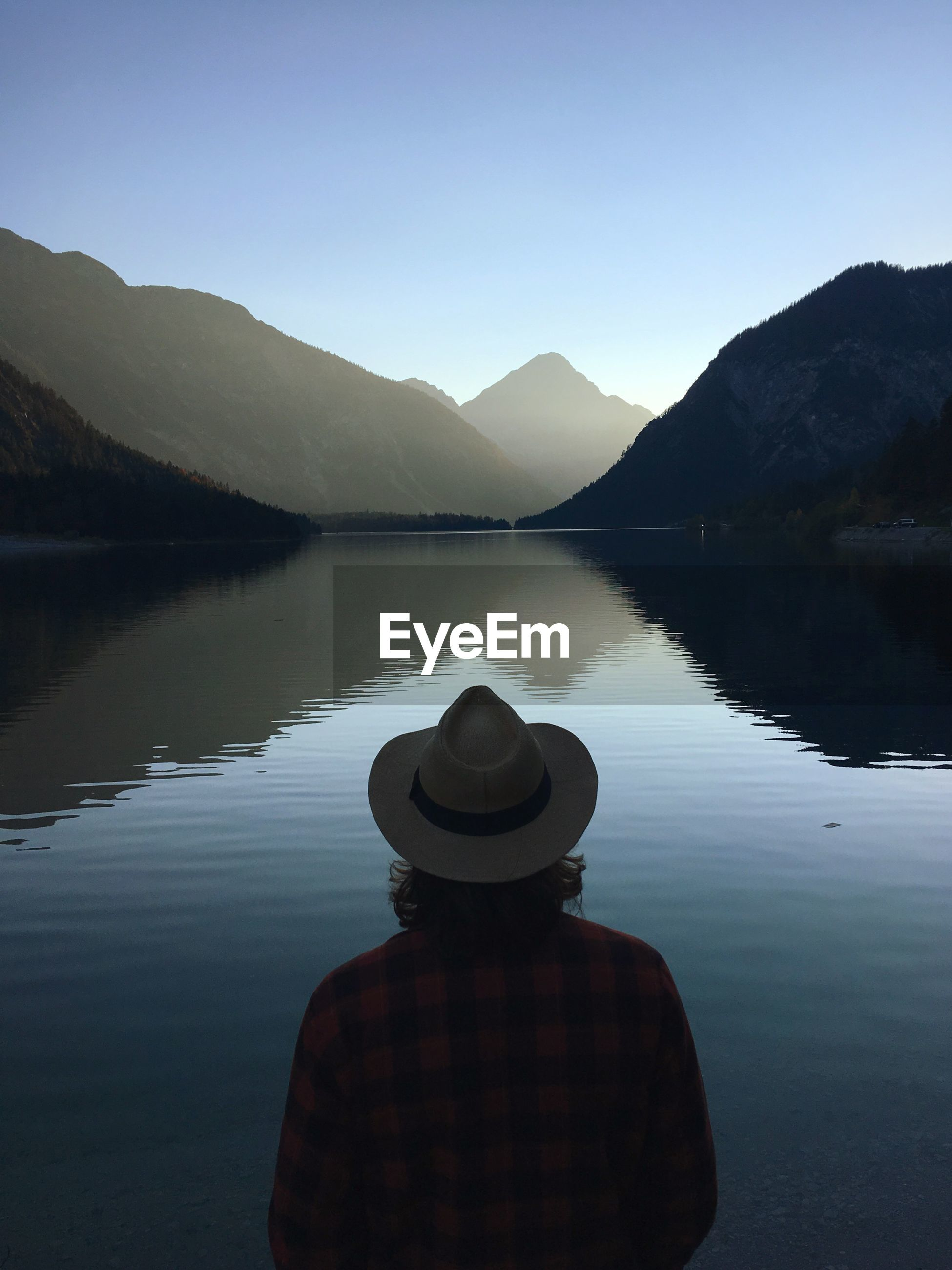 Rear view of man wearing hat while looking at lake against sky